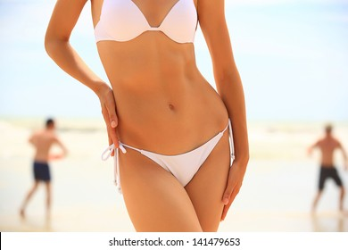 Slim female body in bikini and guys playing fresbee  on the beach