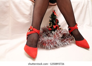 Slim female legs in black fishnet stockings and red shoes with christmas tree and decorations. Sexy Santa girl, concept of romantic date in New year holidays, seductive woman in glamour clothing