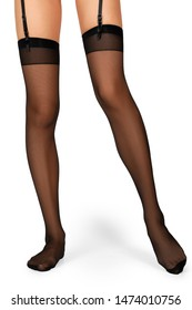 Slim female legs in black seam stockings with garter isolated on white