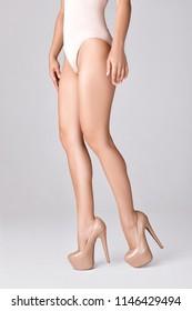 slim female legs wearing high heels on gray background. perfect body in bodysuit