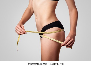 Slim fit happy young woman with measure tape measuring her waist with black underwear, isolated on light gray background. studio shot.