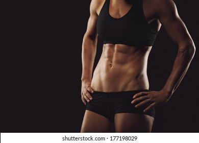 Slim and fit woman belly with hands on hips. Mid section of young tanned woman body with muscular abs on black background with copyspace