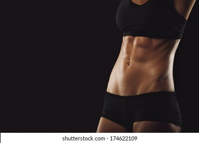 Slim and fit woman belly. Torso of fitness female. Mid section of woman body with muscular abs on black background with copyspace