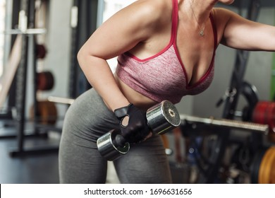 Slim fit woman practicing extension of one arm with a dumbbell in an inclination.