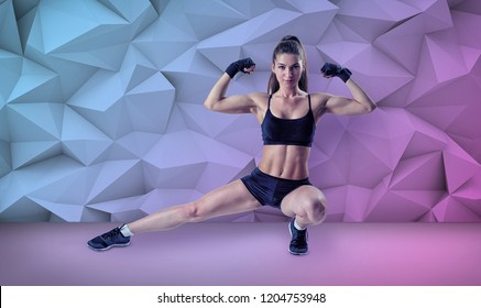 A slim and fit young woman in a low side lunge shows her muscular arms. Fitness and sport. Getting in shape. Bodybuilding for women.