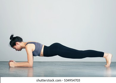 Slim fitnes young girl  doing planking exercise indoors at home gymnastics.