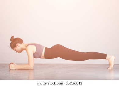 Slim fitnes young girl  doing planking exercise indoors at home gymnastics.  Toned