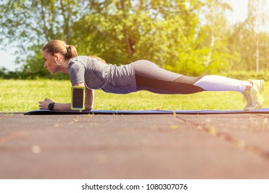 Slim fitnes young girl with ponytail doing planking exercise outdoor