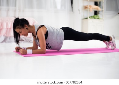 Slim fitness young woman Athlete girl doing plank exercise at home concept training workout crossfit gymnastics cross fit.