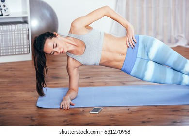 Slim fitness young woman doing side plank exercise at home with smartphone
