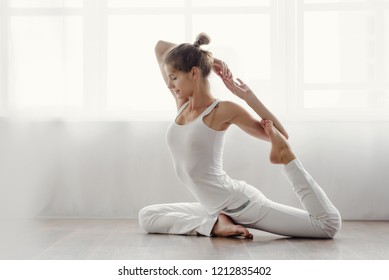 Slim flexible woman doing acrobatic exercise at home