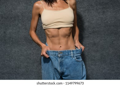 slim girl after diet in old big jeans