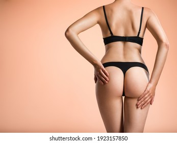 Slim girl in black lingerie posing at the studio. Back view of a female butt. Young  woman with beautiful buttocks. Rear view of a perfect female body.