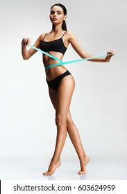 Slim girl in black underwear with a measuring ribbon at the waist. Photo of beautiful  brunette girl with perfect body. Fitness or body care concept