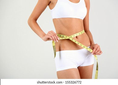 Slim girl with centimeter on gray background