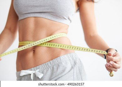 Slim girl with centimeter on white. Closeup woman measuring her waist with tape. Weight loss concept