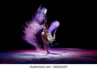 Slim girl dancing in color dust in the dark