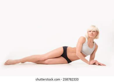 slim girl doing exercises on the floor in the gym. on white isolated background