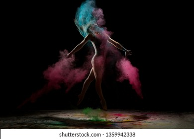 Slim girl jumping in color dust cloud in the dark