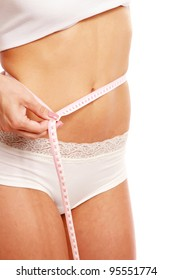 A slim girl measuring her waist, closeup, isolated on white background