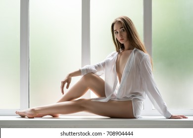 Slim girl on window sill in unbuttoned shirt
