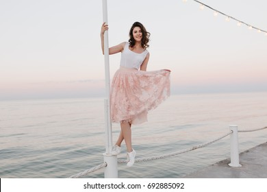 920a821281 Slim girl in pink skirt and white shoes posing with legs crossed and  inspiring smile on
