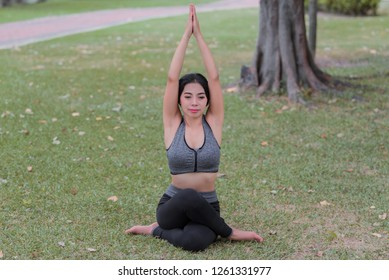 Slim girl play yoga on the lawn at the park,relax in nuture,Asian Girls love health practicing yoga