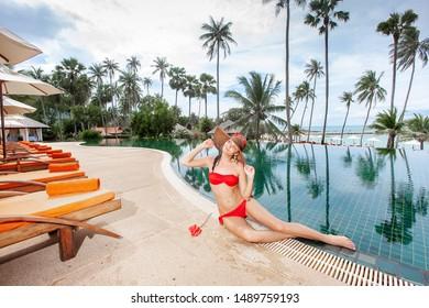 slim girl in a red bikini is relaxing by the pool
