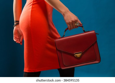 Slim girl in a red dress standing sideways with a vintage bag in his hand taking a step in the studio