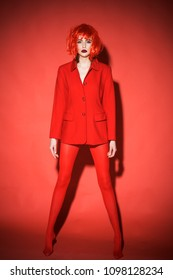Slim girl in red tights and oversize jacket wearing bob style wig standing on her tiptoes, rebellious youth concept. Young female with stylish make-up isolated on red background.