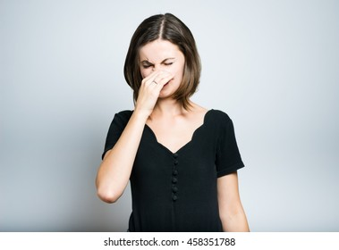 slim girl showing bad smell, studio photo isolated on a gray background
