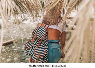 slim girl with a striped backpack sneaking through the palm branches in the hot country of Europe