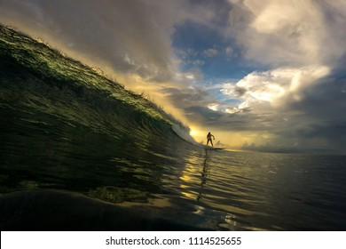 Slim girl surfing in a huge transparent wave against the backdrop of incredible sunset