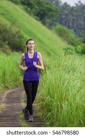 Slim girl in tight sportswear with dark hair running outdoors among green grass summer nature, full front view vertical.
