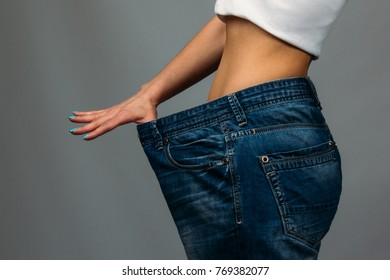 Slim girl trying on large size old jeans