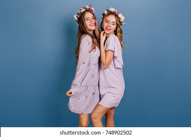 Slim girls in romantic pastel attires posing together in studio. Refined  young woman in flower wreath standing near long-haired friend on blue background.