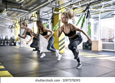 Slim girls are training intensive with goflo-trainers in the gym on the windows background. They are wearing the multicolored sportswear: pants, tops and sneakers. Horizontal.