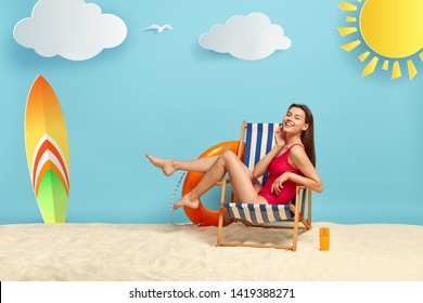 Slim good looking female rests in deckchair at beach, shows slender legs, wears red bikini, has glad look, charming smile, bottle of sunscreen on sand, surfboard has unforgettable summer holiday