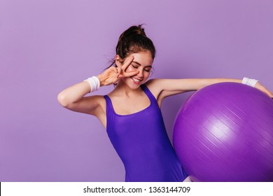 Slim gymnast girl holds fitball and shows peace sign on purple background