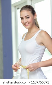 Slim and healthy young woman measuring her perfect waist with a yellow tape measure. lifestyles concept.
