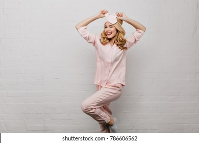 Slim lady in pink night-suit funny dancing isolated on white background. Studio shot of amazing fair-haired girl in cute pajamas fooling around.
