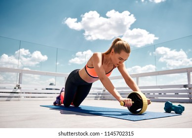Slim lady is training abdominal muscles with wheel. She is looking at outfit while doing effort on open terrace. Workout for being healthy concept