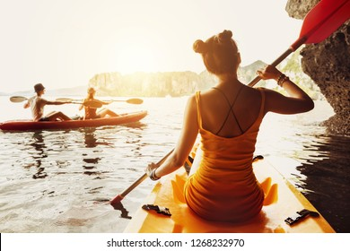 Slim lady walks by kayak at sea bay. Kayaking or canoeing concept with friends