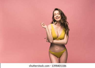 slim laughing girl in yellow swimsuit posing isolated on pink