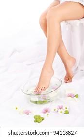 Slim legs of beautiful girl with aromatherapy bowl