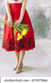 slim legs of woman on high heels with red skirt and spring flowers
