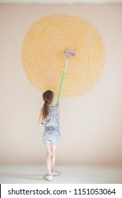 slim little artist caucasian girl painting yellow sun on wall with paint roller