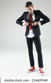 Slim male model having a hard time buttoning small suit jacket on white background