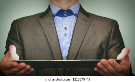 Slim a man (guy) in a suit holding a tablet in his hands. Concept from: Fingers, Unusual background, Business man, Suit, Tie, Novelty, Style, Idea, Tablet.