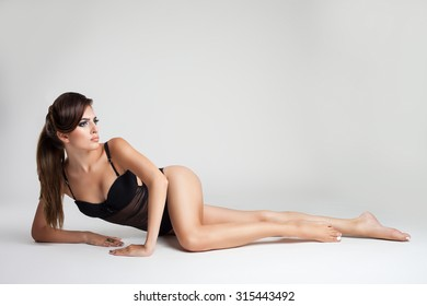 slim model in black bathing suit on a light background